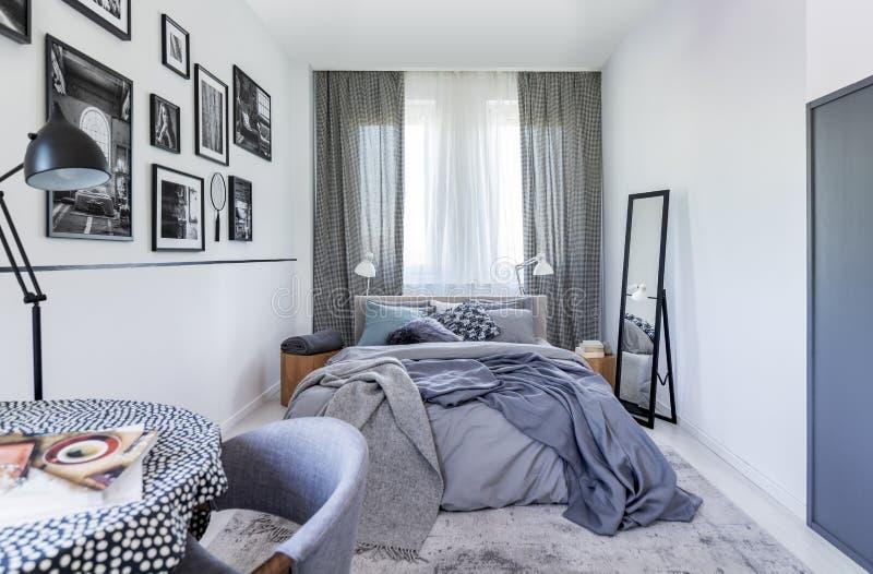 Spiegel nahe bei Bett mit Blättern im Schlafzimmerinnenraum mit schwarzer Lampe und Plakaten Reales Foto stockfotografie