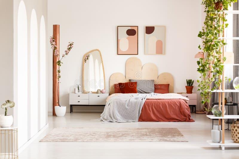 Spiegel op kabinet naast oranje bed in het kader van affiches in helder bed stock afbeeldingen
