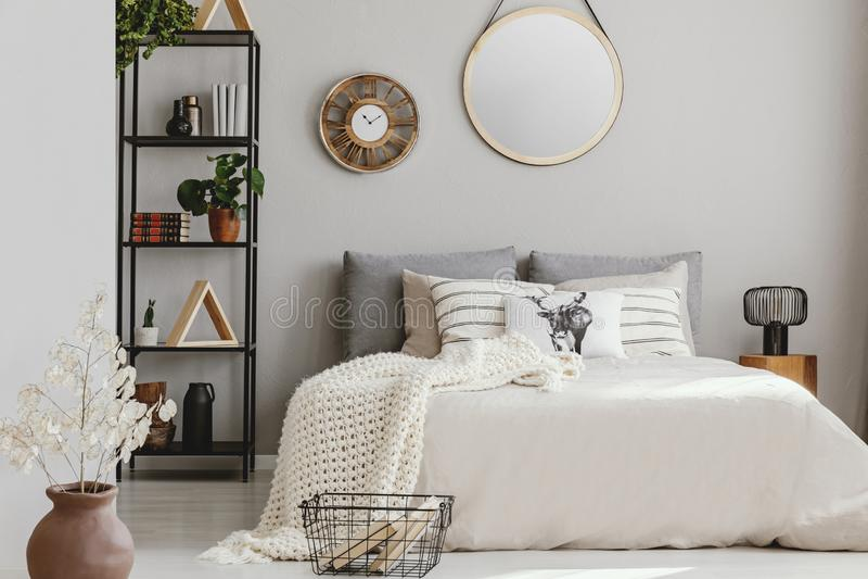 Spiegel und hölzerne Uhr auf der Wand des eleganten Schlafzimmers mit beige Bettwäsche und weißer warmer Decke, wirkliches Foto lizenzfreies stockfoto