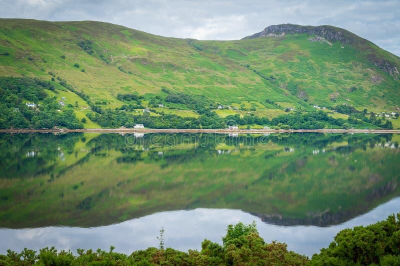 Spiegel zoals bezinningen over Loch Bezem in een bewolkte ochtend stock afbeelding