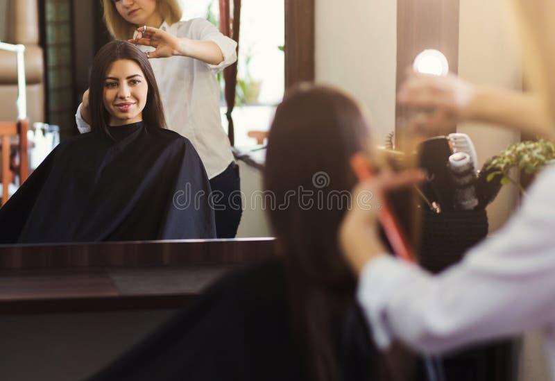Spiegelbezinning van jonge vrouw in salon stock afbeeldingen