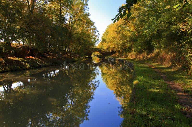Spiegelbezinning van Overspannen Brug en de herfstbomen in het Grote Unie Kanaal royalty-vrije stock foto's