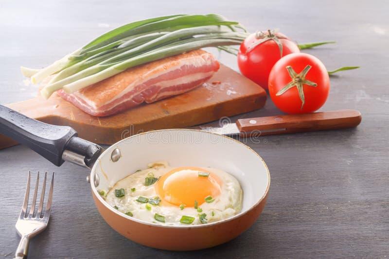 Spiegelei in einer Wanne, Speck, Tomaten und Frühlingszwiebeln werden zum Frühstück gekocht stockfotos
