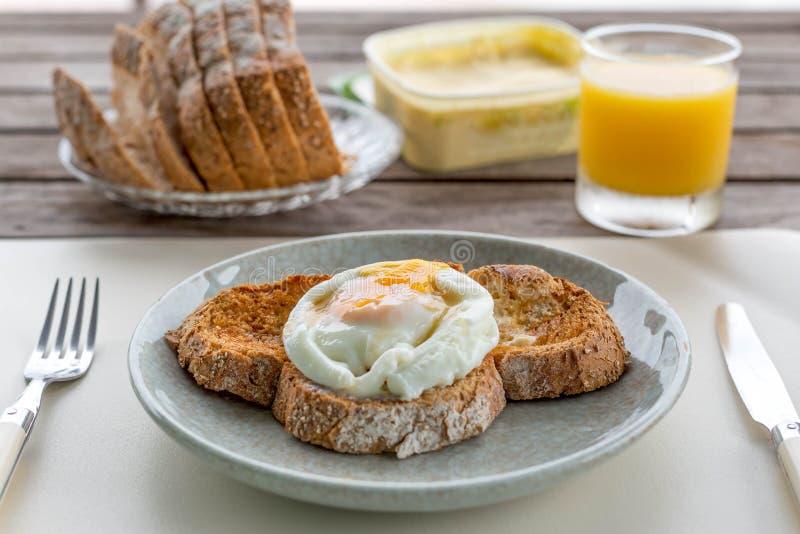 Spiegeleier des Frühstücks auf krustigem Toastbrot mit Orangensaft a stockfotografie