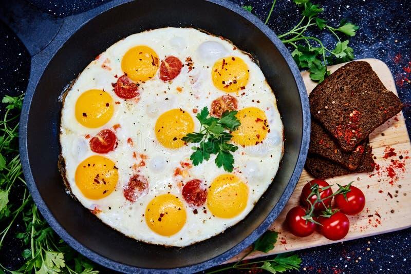 Spiegeleier in einer Bratpfanne mit Kirschtomaten und -brot zum Frühstück auf einem schwarzen Hintergrund stockbilder