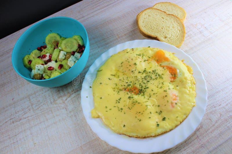 Spiegeleier mit geschmolzenem Käse auf der weißen Platte mit dem Gemüsesalat auf der Seite im blauen Teller mit zwei Stücken Brot lizenzfreies stockbild