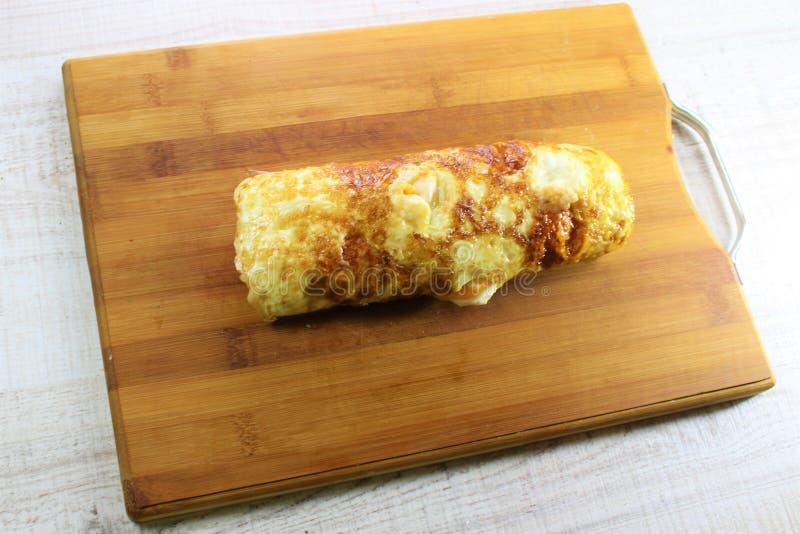 Spiegeleiomelettrolle füllte mit Käse und Zucchini mit dem weißen hölzernen Hintergrund stockfotografie
