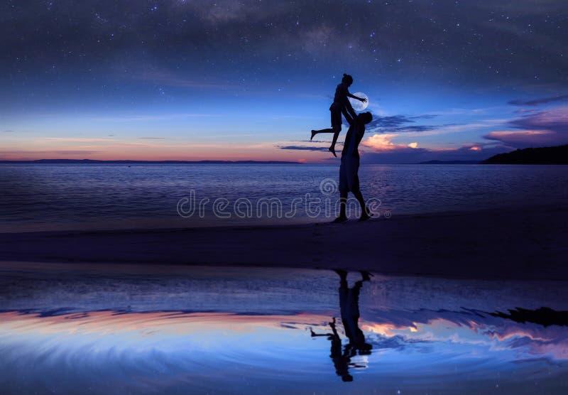 Spiegelreflexion des Schattenbildvaters und -tochter auf dem Strand mit Million frühem Morgen der Sterngalaxie und des blauen Him stockbilder