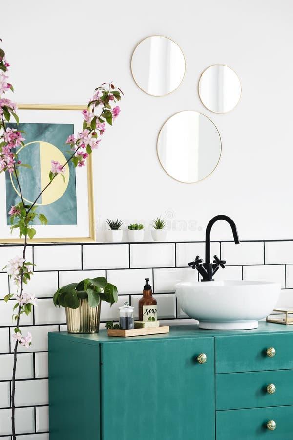 Spiegels en affiche boven groen kabinet in modern badkamersbinnenland met installaties Echte foto stock fotografie