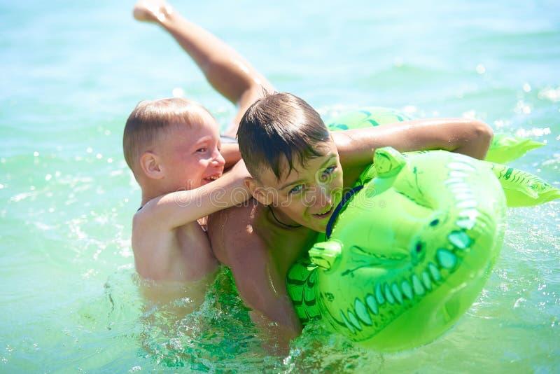 Spiel des jugendlich Jungen und des kleinen Jungen im Wasser stockbilder