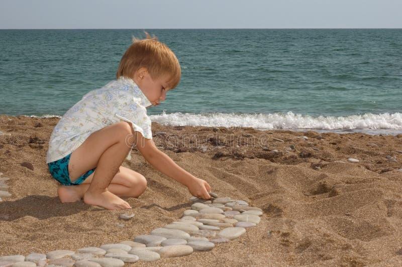 Spiel des kleinen Jungen auf dem Strand stockfotos
