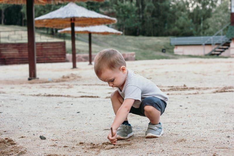 Spiel des kleinen Jungen mit Sand auf Sommerstrand stockfotos