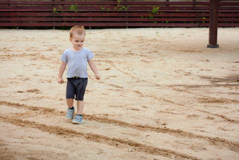 Spiel des kleinen Jungen mit Sand auf Sommerstrand stockfoto