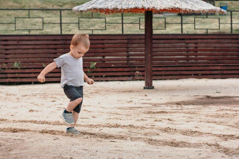 Spiel des kleinen Jungen mit Sand auf Sommerstrand stockbilder