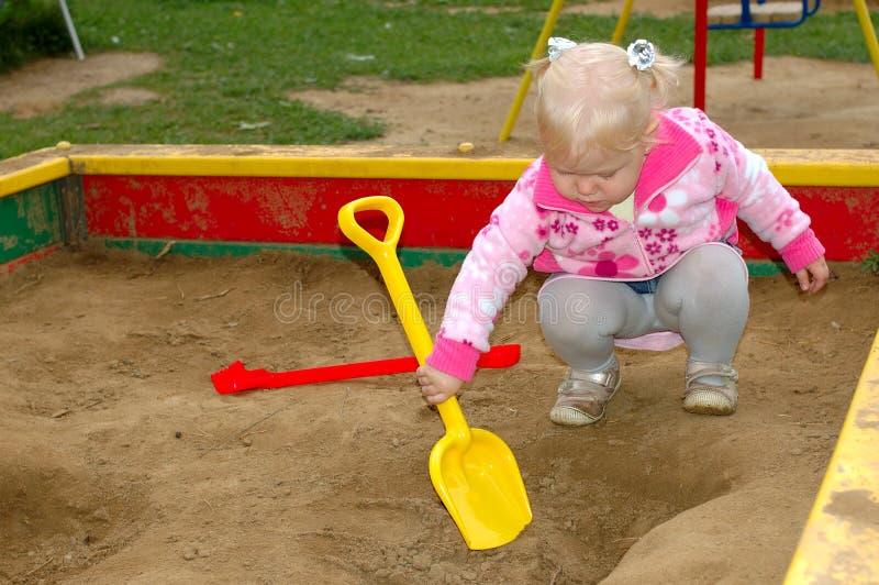 Spiel des recht kleinen Mädchens auf Spielplatz im Park. lizenzfreies stockbild