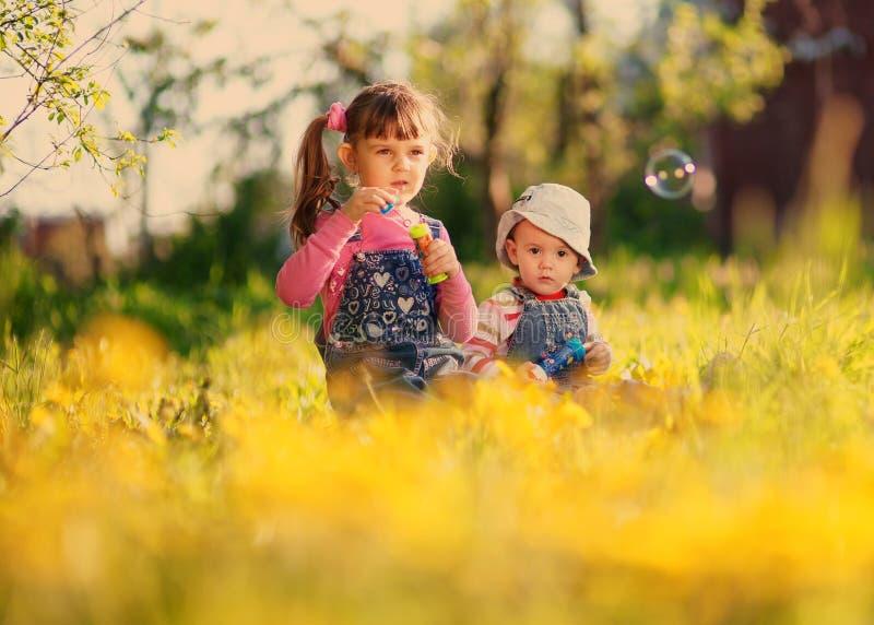 Spiel mit zwei Mädchen mit Seifenblasen im Frühjahr lizenzfreie stockbilder