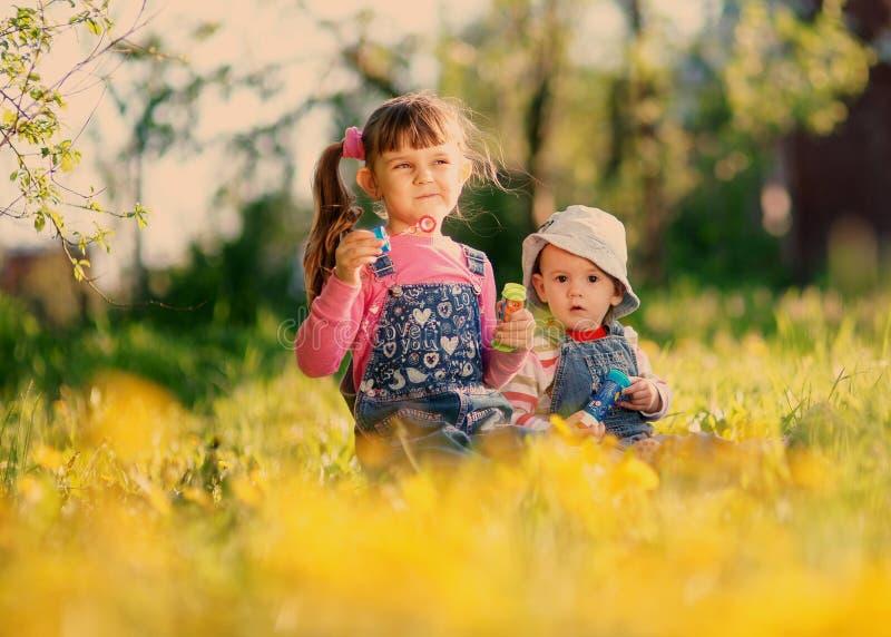 Spiel mit zwei Mädchen mit Seifenblasen im Frühjahr stockbild