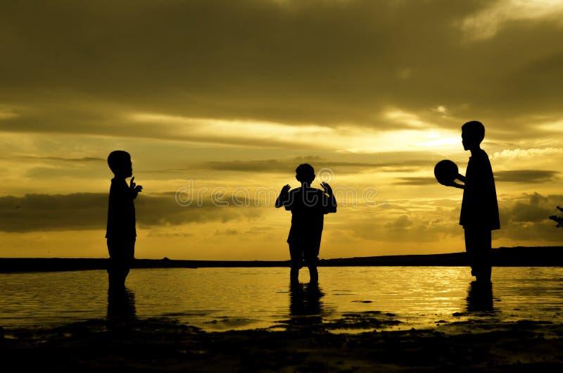 Spiel-Wasserball mit drei Jungen während des Sonnenuntergangsonnenaufgangs Sand und Reflexion auf Wasser stockbilder
