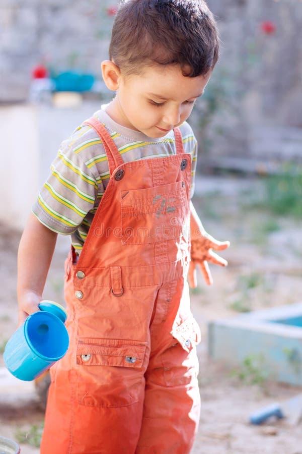 Spiele des kleinen Jungen mit Wasser stockfoto