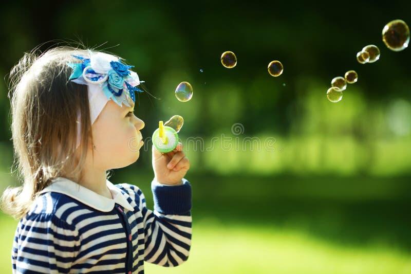 Spiele des kleinen Mädchens mit Blasen stockbild