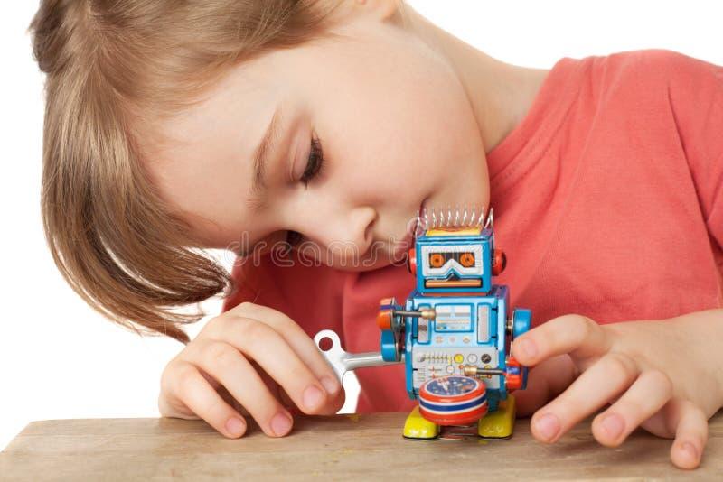 Spiele des kleinen Mädchens mit dem Uhrwerkroboter getrennt stockfotografie