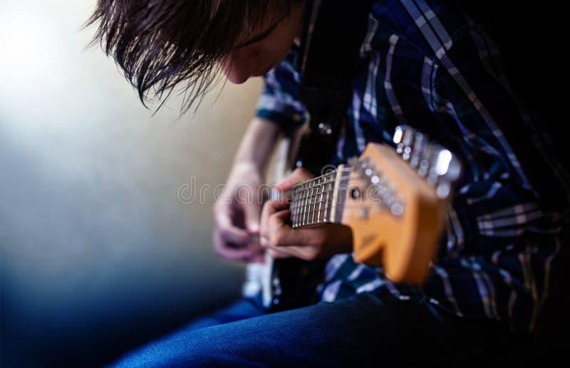 Spielen der elektrischen Gitarre Junge Männer, die E-Gitarre spielen lizenzfreie stockfotos
