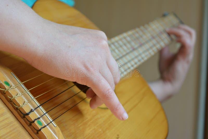 Spielen der Gitarrenmenschenhand lizenzfreie stockfotografie