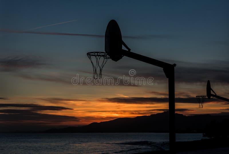 Spielen des Basketballs im Sonnenuntergang lizenzfreie stockfotos