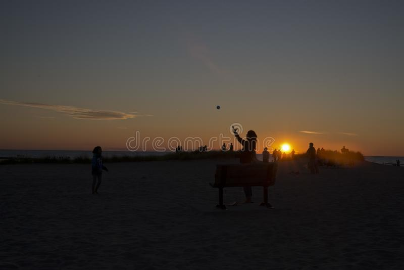 Spielen des Fanges bei Sonnenuntergang auf den Ufern des Michigansees lizenzfreie stockbilder