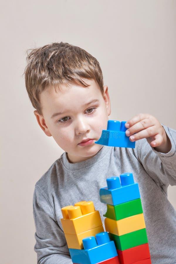 Spielen des kleinen Jungen mit farbigen Würfeln stockfotografie