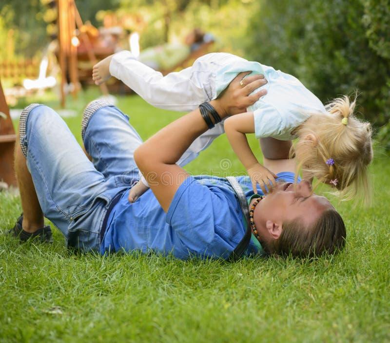 Spielen des kleinen Mädchens im Freien mit ihrem Vater stockfotos