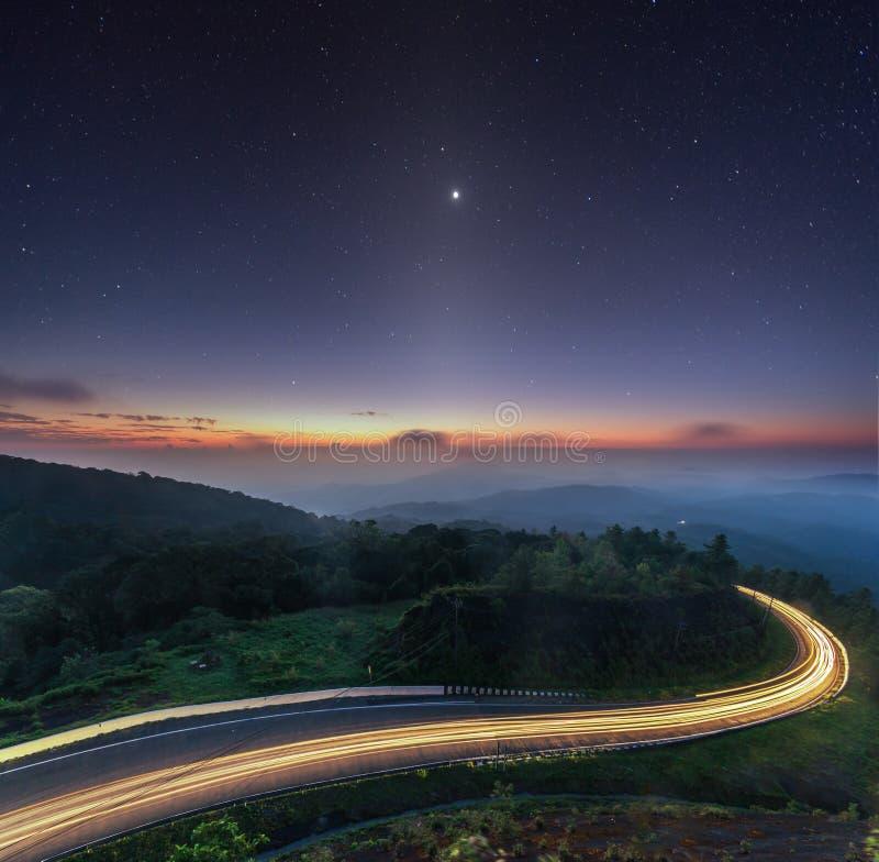 Spielen erstaunliche Kurvenstraße des Natursonnenaufganghintergrundes und zodiacal Licht Dämmerungs-Farblange Belichtung des näch stockbild