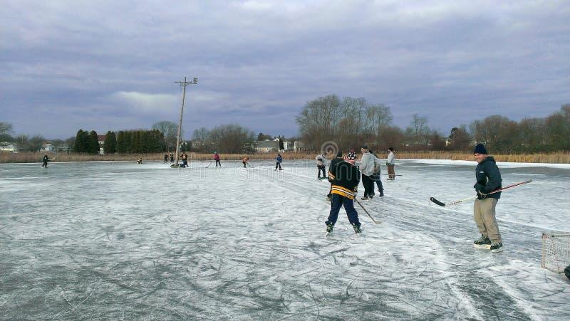 Spielen etwas Teichhockeys im Freien im Winter stockbilder