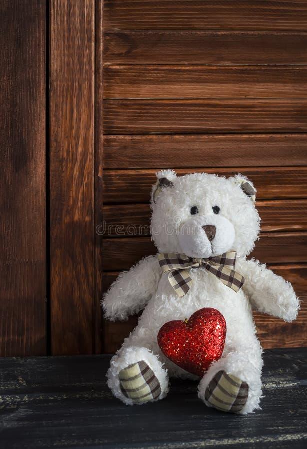 Spielen Sie Bären und rotes Herz auf einer dunklen Holzoberfläche Junger Mann, der seiner Freundin einen roten Geschenkkasten gib lizenzfreie stockfotos