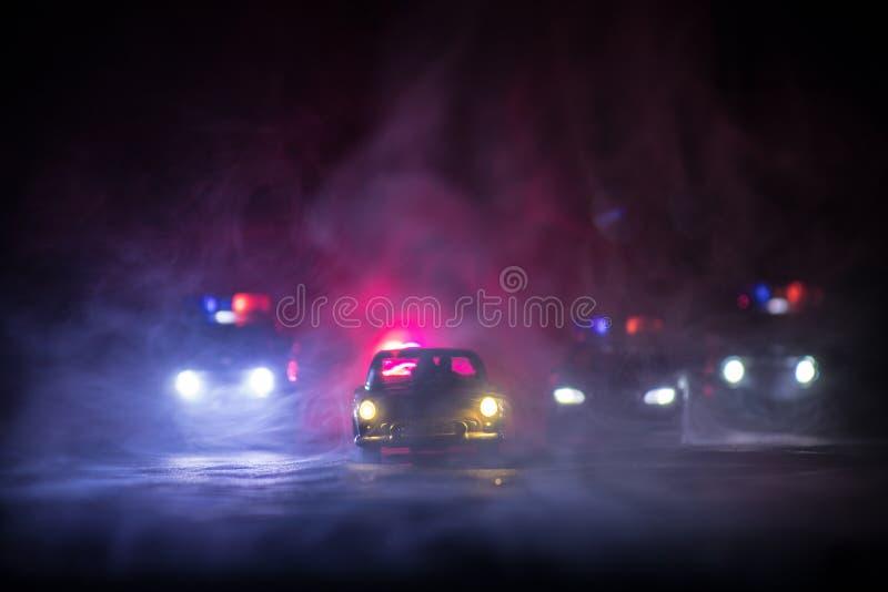 Spielen Sie BMW-Polizei und Kreuzerautos Toyotas FJ, die ein Ford Thunderbird-Auto nachts mit Nebelhintergrund jagen Spielzeugdek stockfotografie