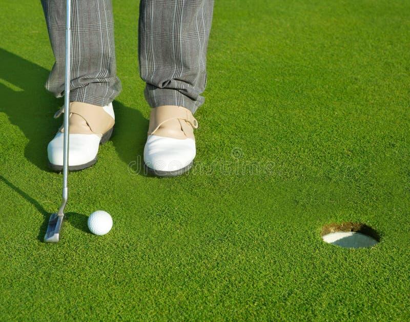 Spielen Sie den grünen Lochkursmann golf, der kurze Kugel setzt lizenzfreie stockfotos