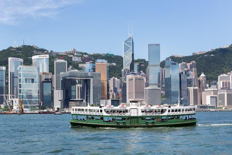 Spielen Sie Fähre in Victoria Harbour mit Hong Kong-Skylinen im Hintergrund die Hauptrolle lizenzfreies stockbild