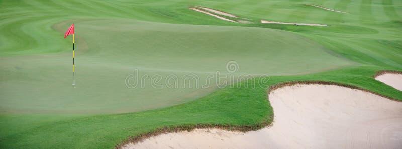 Spielen Sie Grün mit roter Fahne Golf lizenzfreie stockfotos