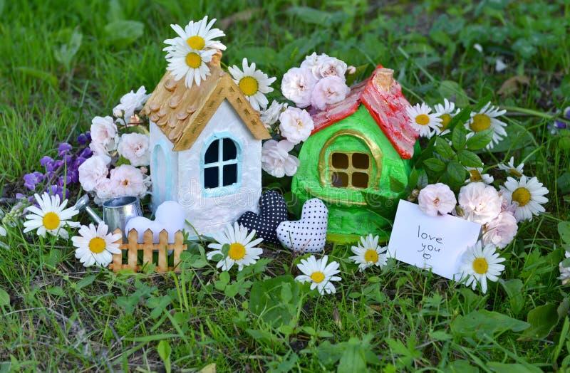 Spielen Sie Häuser mit Anmerkung und simsen Sie Liebe Sie, Dekorationen, Blumen im Gras lizenzfreie stockfotos