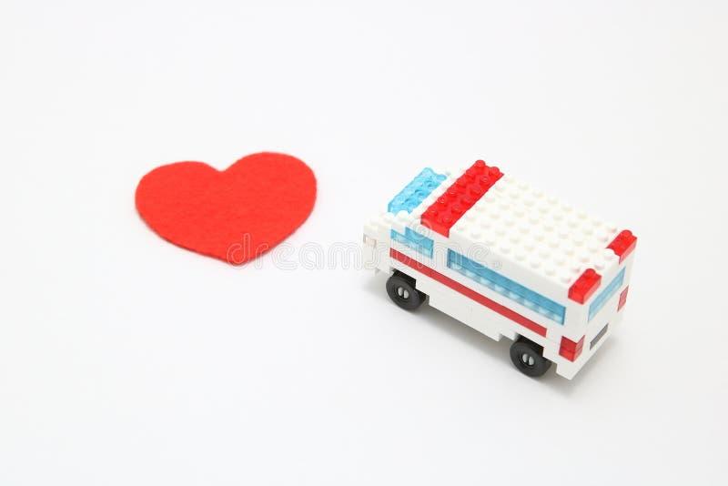 Spielen Sie Krankenwagenauto und abstraktes rotes Herz auf weißem Hintergrund stockbild