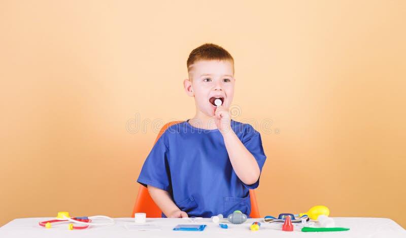 Spielen Sie Spiel r Gesunde Lebensdauer Kinderkleiner Doktor sitzen Tabelle mit Stethoskop und medizinische lizenzfreies stockfoto