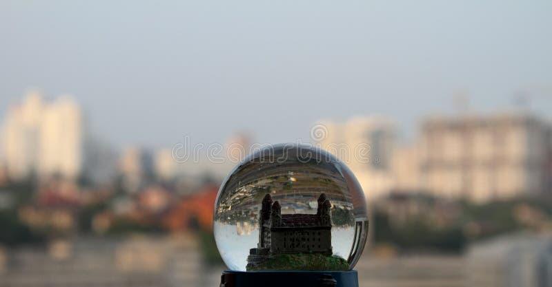 Spielen Sie Stadt im Glasschneeball über wirklichen Gebäuden lizenzfreies stockbild