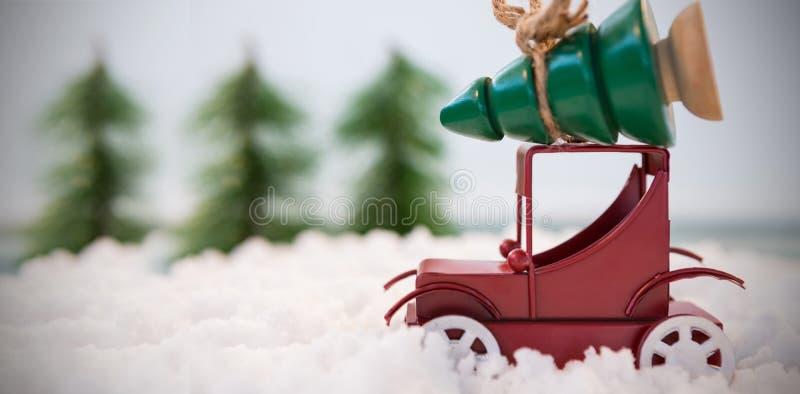 Spielen Sie tragenden Weihnachtsbaum des Autos auf gefälschtem Schnee stockbild