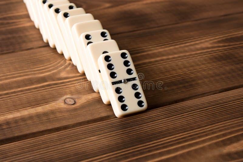 Spielen von Dominos auf einem Holztisch Rote Stücke, die, getrennt auf weißem Hintergrund abfallen lizenzfreie stockbilder