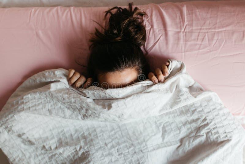 Spielende junge Frau versteckt Gesicht unter Decke, während sie in einem gemütlichen Bett auf weißem Kissen liegt, ziemlich neugi lizenzfreie stockbilder