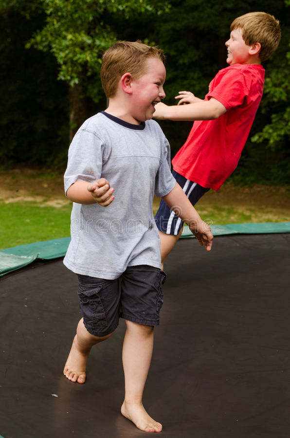 Spielende Kinder beim auf Trampoline draußen springen lizenzfreies stockbild