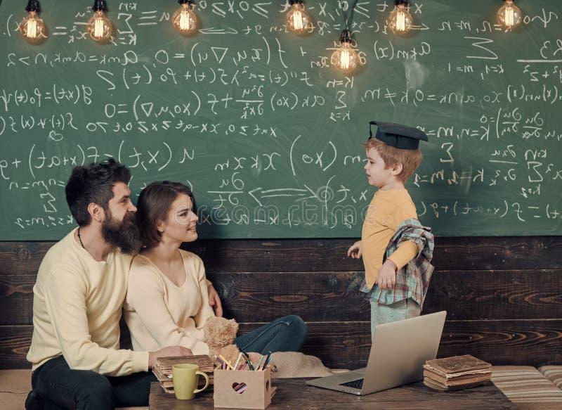 Spielende Kinder - glückliches Spiel Homeschoolings-Konzept Intelligentes Kind in der graduierten Kappe mag studieren Eltern, die stockbild