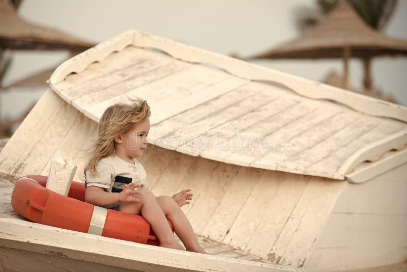 Spielende Kinder - glückliches Spiel Kleines Kind des Jungen, das im Rettungsring sitzt lizenzfreie stockbilder