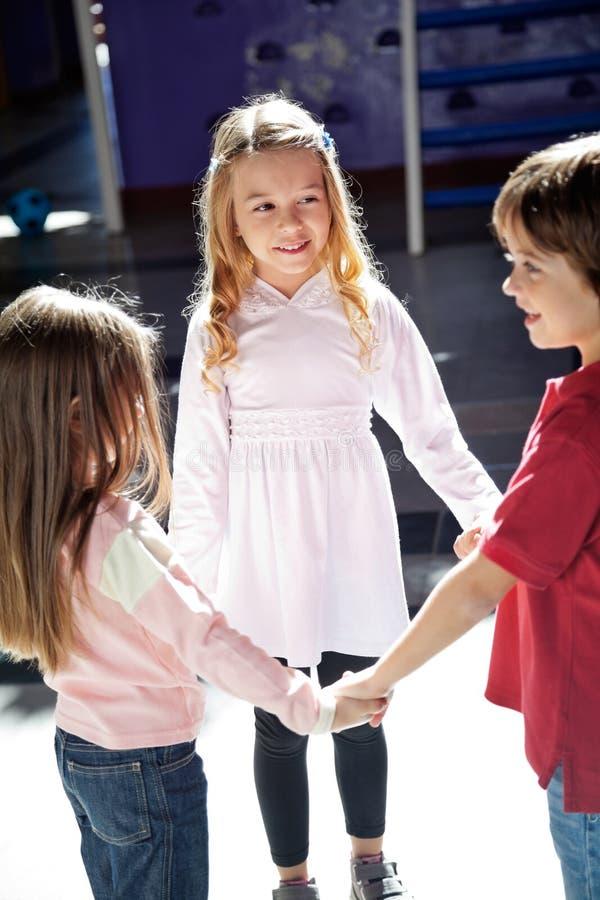 Spielende Kinder während Händchenhalten in der Vorschule stockbild