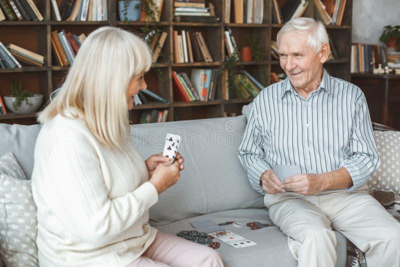 Spielende Spielkarten des älteren der Paare Ruhestandskonzeptes zusammen zu Hause lizenzfreie stockfotografie